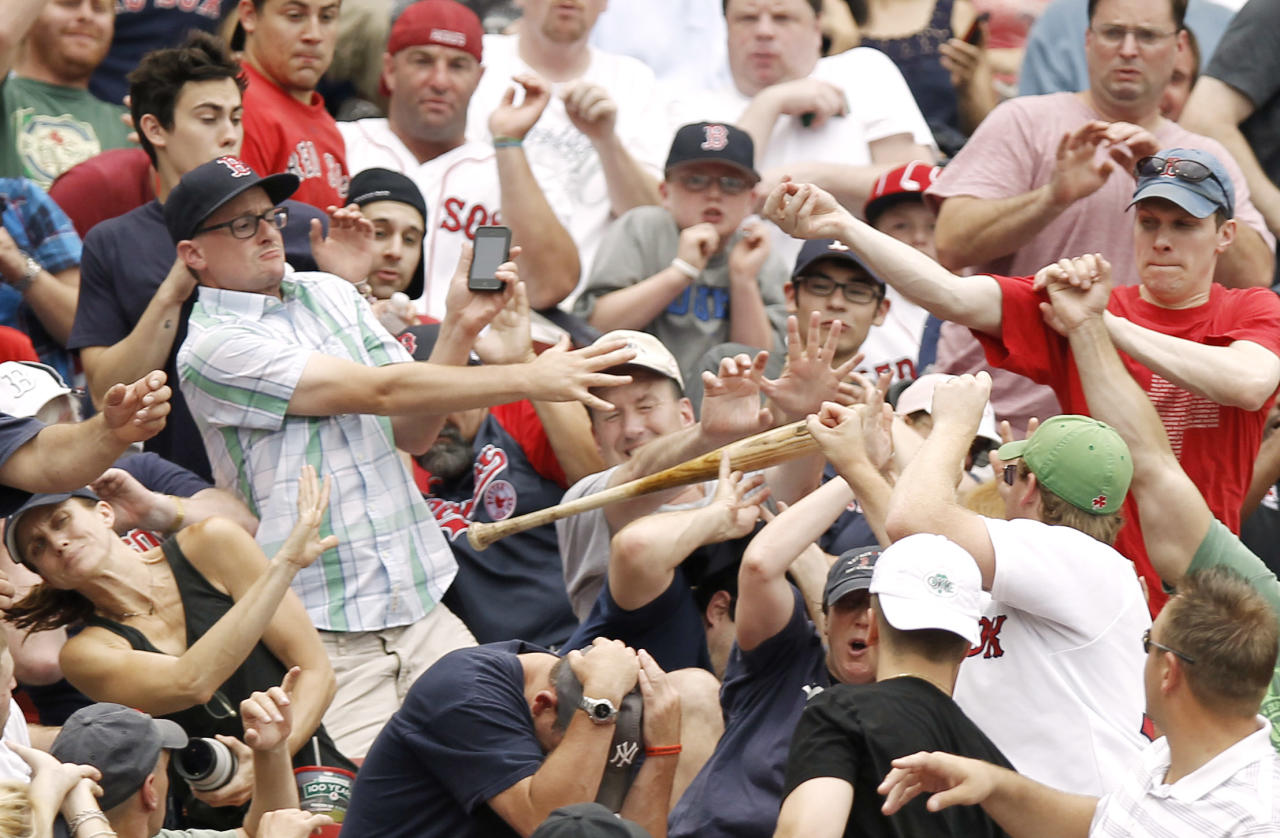 BOSTON, MA - JULY 7:  Fans react as the bat of Kelly Shoppach #10 of the Boston Red Sox goes flying into the stands during the third inning of game one of a doubleheader against the New York Yankees at Fenway Park on July 7, 2012 in Boston, Massachusetts.  (Photo by Winslow Townson/Getty Images)