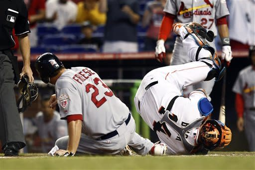 Miami Marlins catcher John Buck falls backwards after tagging St. Louis Cardinals' David Freese (32) out at home during the first inning of a baseball game in Miami, Wednesday, June 27, 2012. (AP Photo/J Pat Carter)