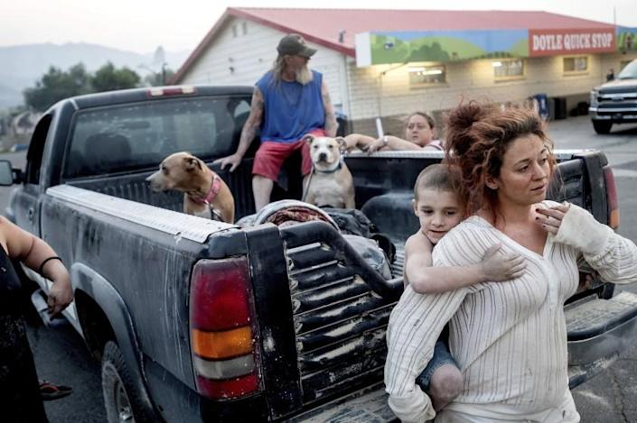 Destiney Barnard holds Raymond William Goetchius while stranded at a gas station near the Dixie Fire on Tuesday, Aug. 17, 2021, in Doyle, Calif. Barnard was helping Goetchius and his family evacuate from Susanville when her car broke down. (AP Photo/Noah Berger)