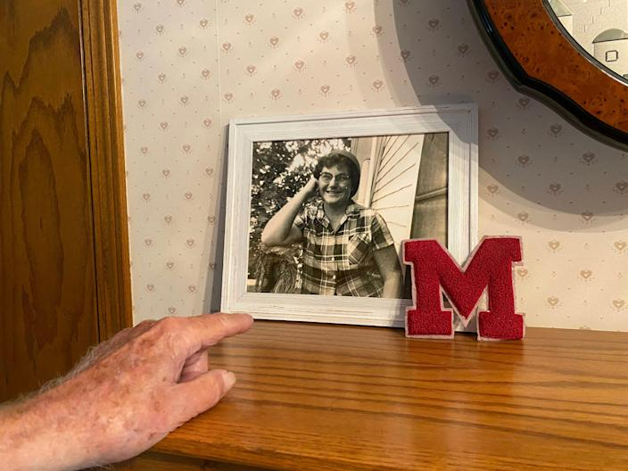Frank Soyez points to a picture of his wife, who is wearing his helmet from his service time in World War II.