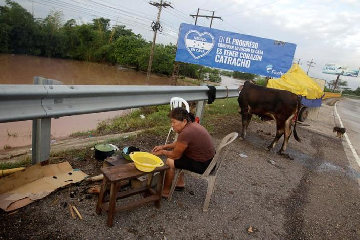 A woman cooks on the side of a highway after losing her home due to heavy rains caused by Hurricane Iota, in El Progreso