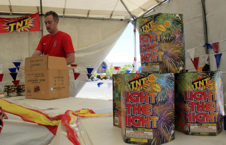 FILE - In this July 1, 2014, file photo, Nathan Farmer unpacks dozens of boxes of fireworks to sell at a roadside stand in Albuquerque, N.M. With fewer professional celebrations on July 4, 2020, many Americans are bound to shoot off fireworks in backyards and at block parties. And they already are: Sales have been booming. (AP Photo/Susan Montoya Bryan, File)