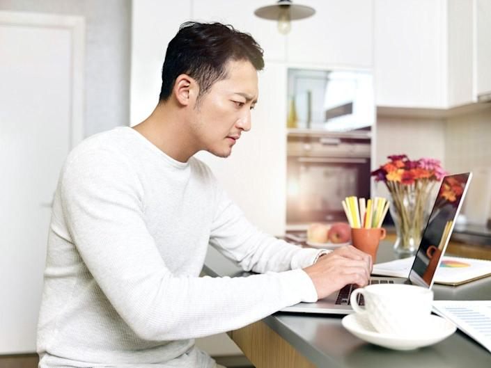 man working from home sitting at kitchen counter using laptop computer