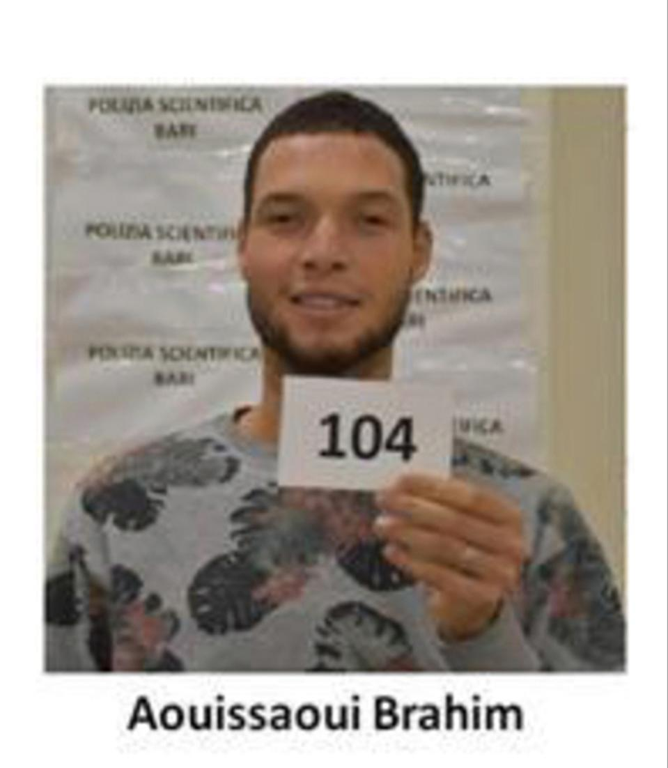 Brahim Aouissaoui holding a card with the number 104 on it while smiling.