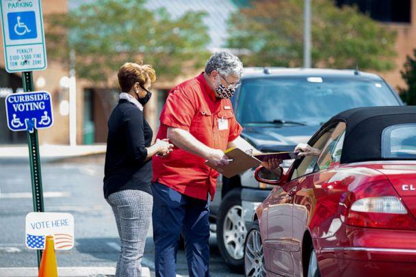 PHOTO: Election workers Tim McLeod and Cybil Usual assist a voter casting their ballot curbside on the first day of early voting at the Office of Elections satellite location at Southpoint in Spotsylvania, Va., Sept. 18, 2020. (Mike Morones/The Free Lance-Star via AP, FILE)