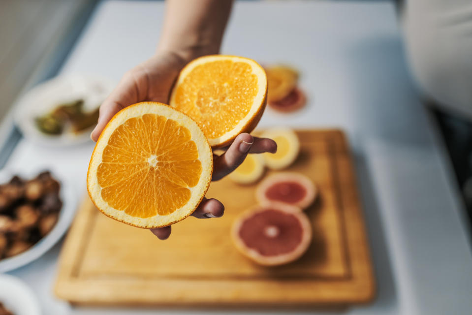 Female hand  holding fresh Orange in her kitchen. Home grown ripe clementines, organic food that the girl holds in her hand. Woman holding two halves of Orange citrus fruit
