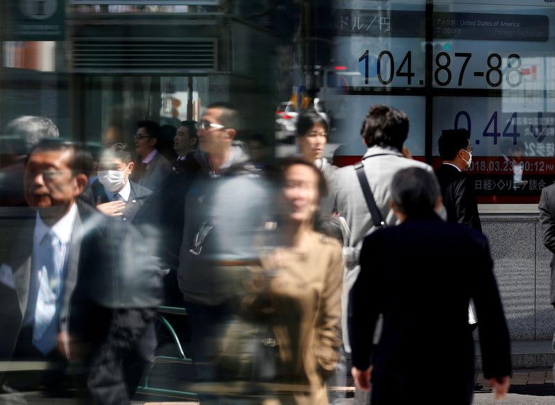 People walk past an electronic board showing exchange rate between Japanese Yen and U.S. Dollar outside a brokerage at a business district in Tokyo, Japan, March 23, 2018. REUTERS/Toru Hanai