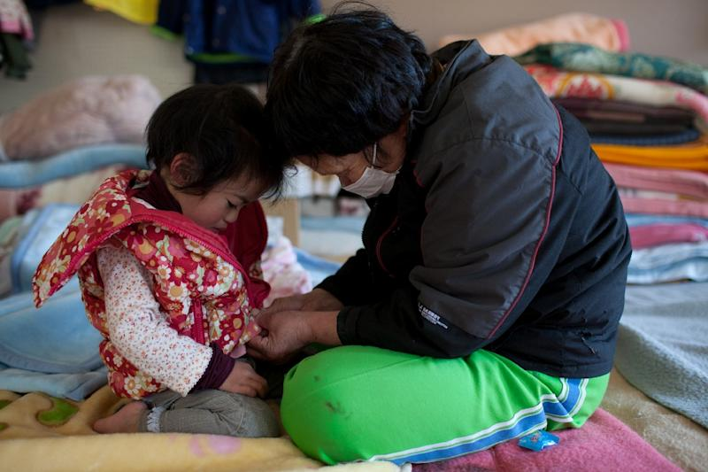 70 year old tsunami survivor Chiiko Nakanome, takes care of her 2 year old granddaughter, Ena, at an evacuation centre in Rikuzentakata city, Iwate prefecture on April 17, 2011 (AFP Photo/Yasuyoshi Chiba)