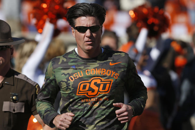 Oklahoma State head coach Mike Gundy runs onto the field before an NCAA college football game against Kansas in Stillwater, Okla., Saturday, Nov. 16, 2019. (AP Photo/Sue Ogrocki)
