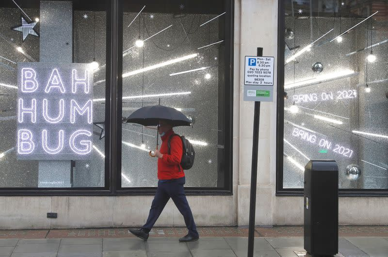 FILE PHOTO: A man walks past a shop window with a Christmas theme amid the coronavirus disease (COVID-19) outbreak in London