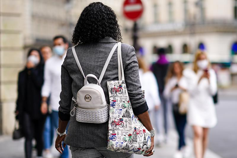 PARIS, FRANCE - JULY 03: A passerby wears a gray blazer jacket, a Michael Kors small backpack, a tote bag with printed bicycles, on July 03, 2020 in Paris, France. (Photo by Edward Berthelot/Getty Images)