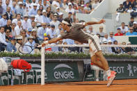 FILE - In this June 4, 2019, file photo, Switzerland's Roger Federer dives to return a shot in the third set against Switzerland's Stan Wawrinka during their quarterfinal match of the French Open tennis tournament at Roland Garros stadium in Paris. (AP Photo/Michel Euler, File)