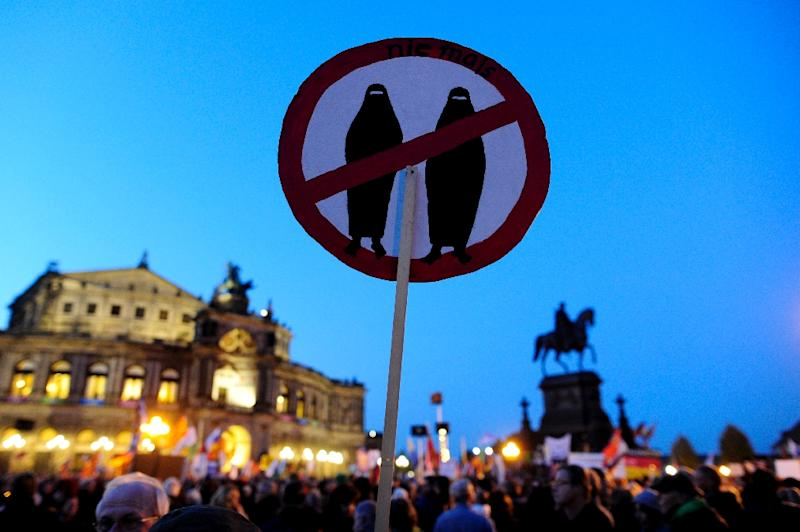 A supporter of the anti-Islam party PEGIDA holds a poster at a protest rally on October 12, 2015 in Dresden, eastern Germany