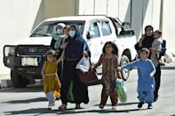 A steady stream of buses was disgorging passengers at Kabul's airport and they were allowed to cross to the American held part for evacuation (AFP/WAKIL KOHSAR)