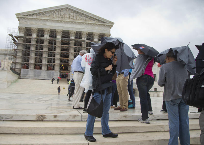 Cynthia Grossman of Lewisville, Colo. holds up her umbrella against the wind and rain while waiting outside the Supreme Court in Washington, Monday, Oct. 7, 2013, on the first day of the 2013-2014 term. The justices take the bench Monday for the start of their new term with important cases about campaign contributions, housing discrimination and government-sanctioned prayer already on tap. Abortion, contraceptive coverage under the president's new health care law and mobile phone privacy also may find their way onto the court's calendar. (AP Photo/ Evan Vucci)