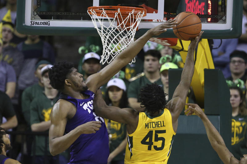 TCU center Kevin Samuel, left, defends a shot by Baylor guard Davion Mitchell, right, in the first half of an NCAA college basketball game, Saturday, Feb. 1, 2020, in Waco, Texas. (AP Photo/Rod Aydelotte)