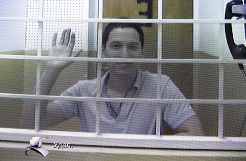 FILE - In this Wednesday, Aug. 21, 2019 file photo, Aidar Gubaidulin waves at the camera as he takes part in a court hearing via a video link in Moscow, Russia. Russian prosecutors on Wednesday Sept. 18, 2019, are asking to release protester Aidar Gubaidulin, facing years in prison for assaulting police following a mounting public campaign in support of anti-government activists and even bystanders caught up in an opposition rally. (AP Photo/Dmitry Serebryakov, File)