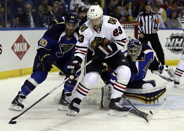 Chicago Blackhawks' Kris Versteeg,center, handles the puck as St. Louis Blues goalie Ryan Miller, right, and Maxim Lapierre, left, defend during the first period in Game 5 of a first-round NHL hockey playoff series Friday, April 25, 2014, in St. Louis. (AP Photo/Jeff Roberson)