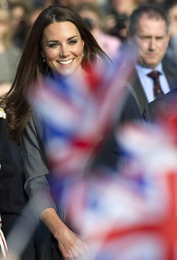 Kate, Duchess of Cambridge is seen through flags being waved by children as she arrives at an art gallery in south London Thursday March 15 2012 for an official visit. (AP Photo/ Mark Richards, Pool)