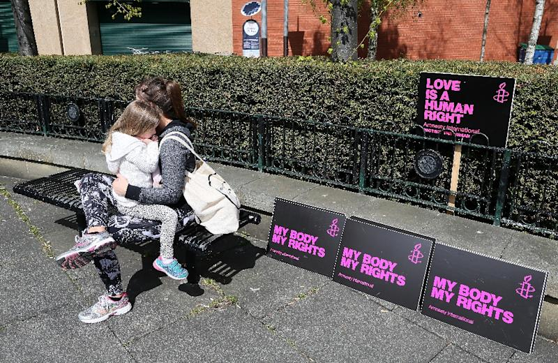 A mother and daughter await the start of a pro-choice demonstration through Belfast city centre on April 30, 2016 (AFP Photo/Paul Faith)