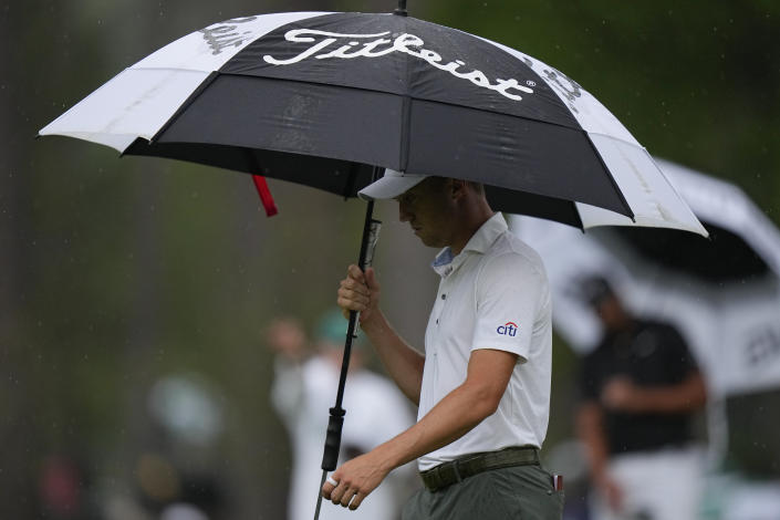 Justin Thomas protects himself from the rain as we walks on the 15th hole during the third round of the Masters golf tournament on Saturday, April 10, 2021, in Augusta, Ga. (AP Photo/Matt Slocum)