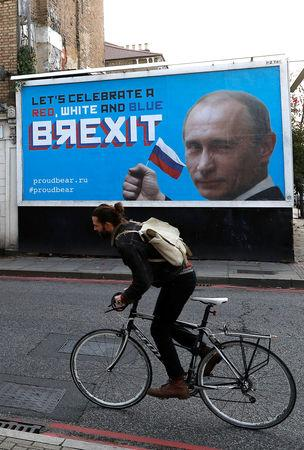 A man cycles past a billboard poster in London, Britain, November 8, 2018. REUTERS/Peter Nicholls