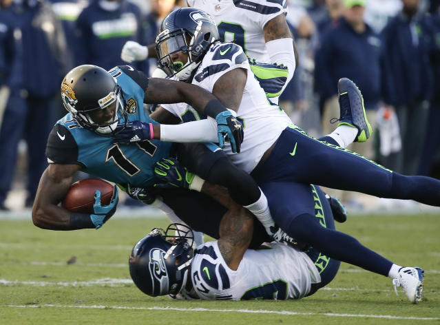 FILE - In this Dec. 10, 2017, file photo, Jacksonville Jaguars wide receiver Marqise Lee (11) is tackled by Seattle Seahawks cornerback Shaquill Griffin, top right, and safety Earl Thomas, bottom, after a reception during the first half of an NFL football game, in Jacksonville, Fla. Thomas is putting the pressure on the Seattle Seahawks for a new contract, saying he will not participate in any team activities until his contract situation is resolved. That includes the upcoming mandatory minicamp. (AP Photo/Stephen B. Morton, File)