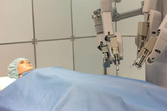 Robotic surgical system next to a patient in a hospital bed.