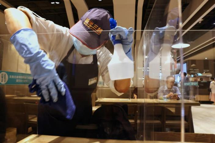 A staff member cleans the plastic partitions at a canteen following the outbreak of coronavirus disease (COVID-19), in Taipei