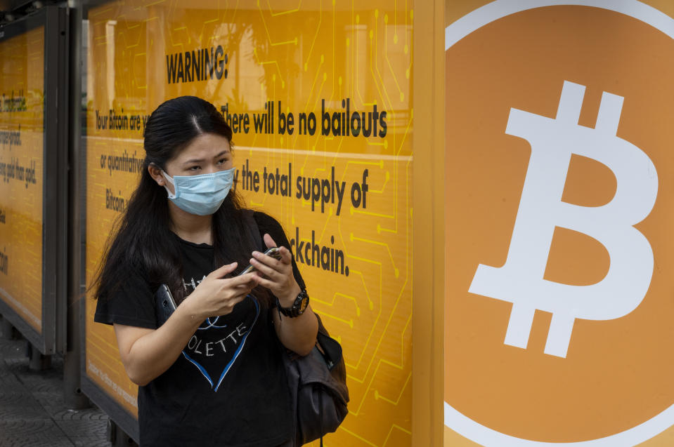 HONG KONG, CHINA - 2020/09/24: A woman wearing a mask stands next to a bus stop covered with Cryptocurrency electronic cash Bitcoin advertisement in Hong Kong. (Photo by Budrul Chukrut/SOPA Images/LightRocket via Getty Images)