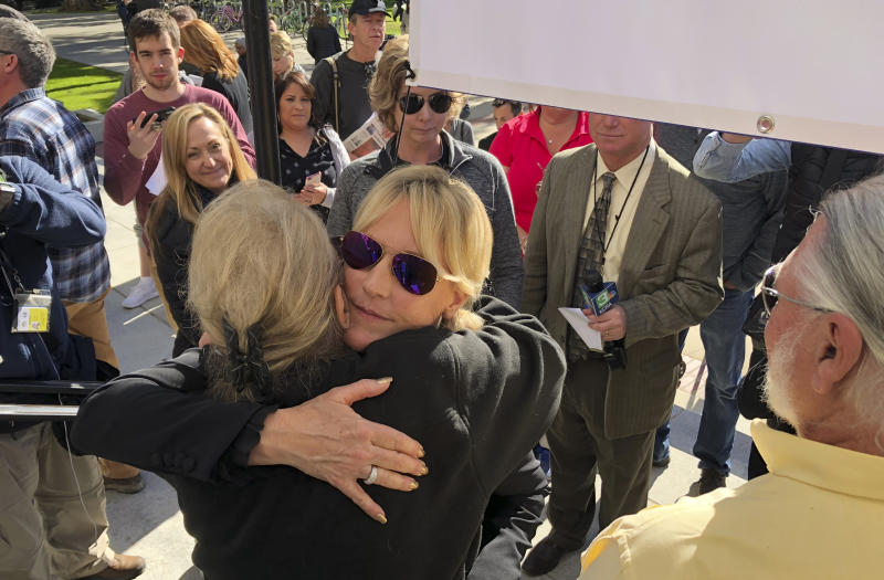 CORRECTS FIRST NAME TO FRANCINE, NOT FRANCHINE - Consumer advocate Erin Brockovich, who famously took on Pacific Gas & Electric Co. in the 1990s, hugs Francine Ehler after standing with wildfire victims and speaking outside the state Capitol Tuesday, Jan. 22, 2019, in Sacramento, Calif. Brockovich is urging California lawmakers not to let PG&E go bankrupt because it might mean less money for wildfire victims. (AP Photo/Kathleen Ronayne)