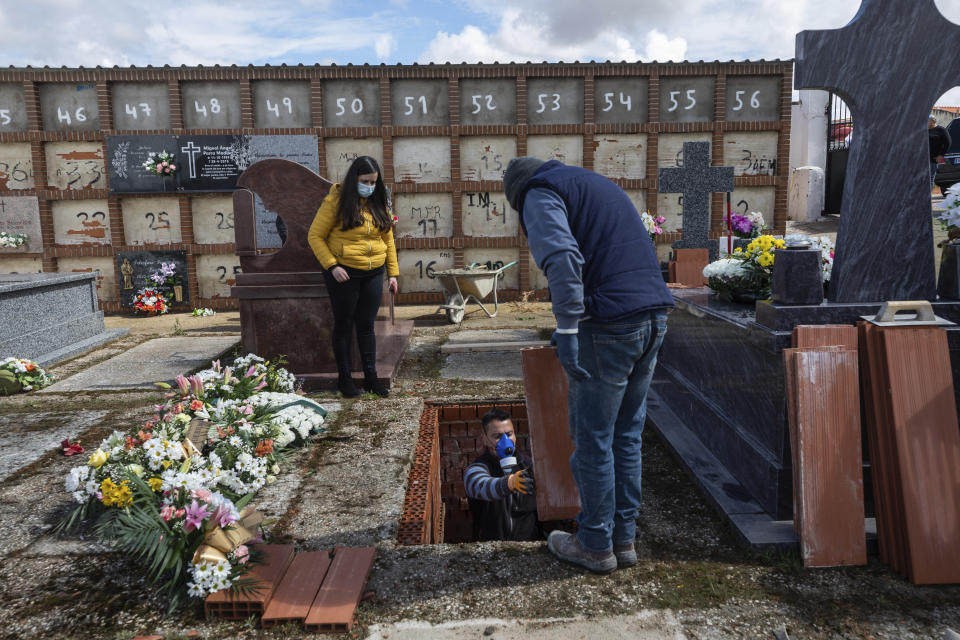 An undertaker prepares a grave during the burial of Rosalia Mascaraque, 86, during the coronavirus outbreak in Zarza de Tajo, central Spain, Wednesday, April 1, 2020. Intensive care units are particularly crucial in a pandemic in which tens of thousands of patients descend into acute respiratory distress. The new coronavirus causes mild or moderate symptoms for most people, but for some, especially older adults and people with existing health problems, it can cause more severe illness or death. (AP Photo/Bernat Armangue)