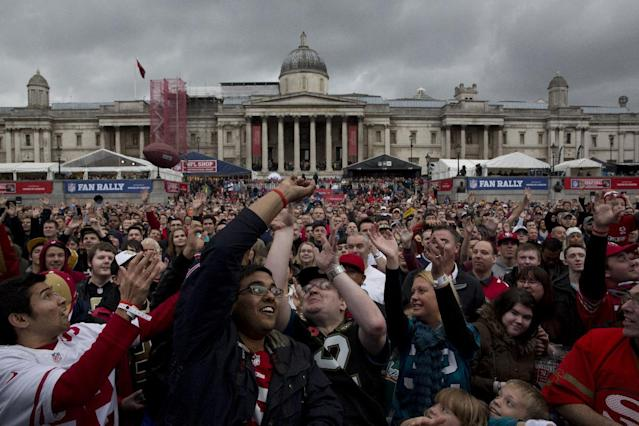 People try and catch a mini ball thrown out to them from the stage during an NFL fan rally in Trafalgar Square, London, Saturday, Oct. 26, 2013. The San Francisco 49ers are due to play the the Jacksonville Jaguars at Wembley stadium in London on Sunday, Oct. 27 in a regular season NFL game. (AP Photo/Matt Dunham)