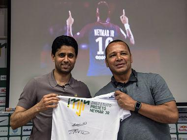 French football team Paris Saint-Germain's (PSG) Qatari president Nasser Al-Khelaifi (L) and Neymar Santos, father of Brazilian superstar and PSG's footballer Neymar Junior, pose for pictures holding a t-shirt of Neymar Junior Institute project, during a press conference, in Praia Grande, Sao Paulo, Brazil on March 13, 2018. Nasser Al-Khelaifi arrived in Brazil to visit the world's most expensive player, Neymar, who broke a bone in his right foot on February 25 and faces weeks of recuperation following surgery. The visit also takes place amid rumors swirling about the striker's intention to quit PSG. / AFP PHOTO / NELSON ALMEIDA