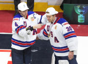 United States' Cam York (4) gives goalie Spencer Knight (30) a gold medal after the team's win over Canada in the championship game in the IIHF World Junior Hockey Championship, Tuesday, Jan. 5, 2021, in Edmonton, Alberta. (Jason Franson/The Canadian Press via AP)