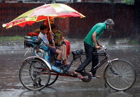 A woman and her children ride in a rickshaw during heavy rains in Chandigarh