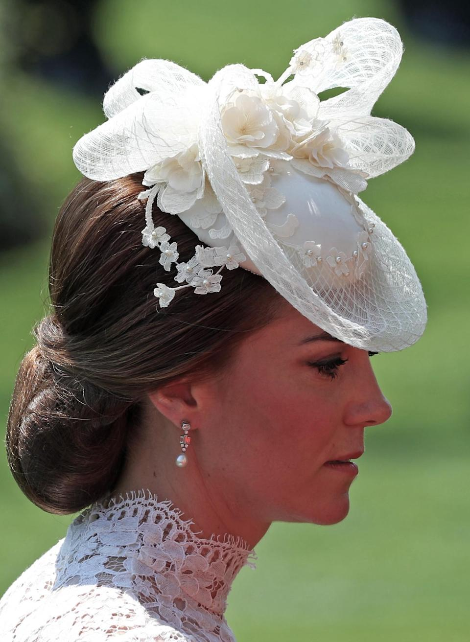 <p>Kate swept her hair up in a chignon and topped it off with a white hat, which featured floral detailing and a bow. The Queen's drop pearl earrings, which were a gift from Bahrain, completed the look. <br><em>[Photo: Getty]</em> </p>