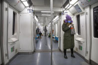 A woman wears safety goggles, a face mask, and rubber gloves as she rides a nearly empty subway train in Beijing, Friday, Feb. 14, 2020. China on Friday reported another sharp rise in the number of people infected with a new virus, as the death toll neared 1,400. (AP Photo/Mark Schiefelbein)