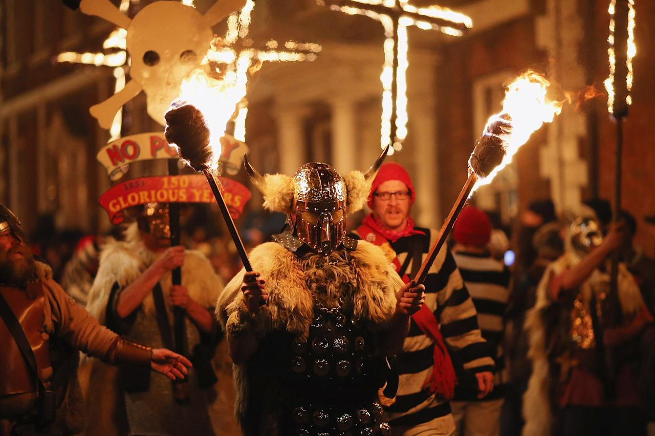 LEWES, ENGLAND - NOVEMBER 05:  Bonfire societies parade through the streets during the Bonfire Night celebrations on November 5, 2012 in Lewes, Sussex in England. Bonfire Night is related to the ancient festival of Samhain, the Celtic New Year. Processions held across the South of England culminate in Lewes on November 5, commemorating the memory of the seventeen Protestant martyrs. Thousands of people attend the parade as Bonfire Societies parade through the narrow streets until the evening comes to an end with the burning of an effigy, or 'guy,' usually representing Guy Fawkes, who died in 1605 after an unsuccessful attempt to blow up The Houses of Parliament.  (Photo by Dan Kitwood/Getty Images)