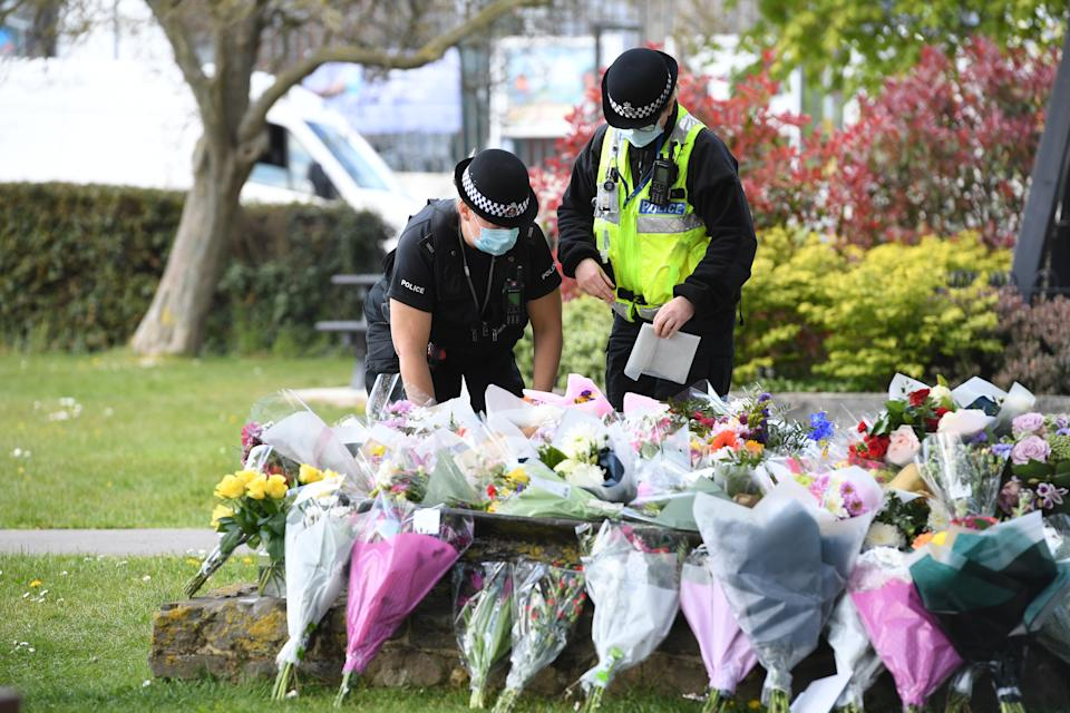Two police officers lay floral tributes in a park in Aylesham village close to the scene in Snowdown, Kent, where the body of PCSO Julia James was found. Picture date: Saturday May 1, 2021.