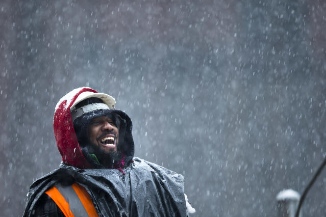 A construction worker smiles as he unloads rebar from a truck during a winter snowstorm, Monday, Feb. 3, 2014, in the Brooklyn borough of New York. After several days of mild weather, snow has returned to the Northeast. (AP Photo/Matt Rourke)