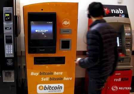 A customer of an Australian bank walks away after withdrawing money from an Automatic Teller Machine located next to a Bitcoin ATM in central Sydney, Australia