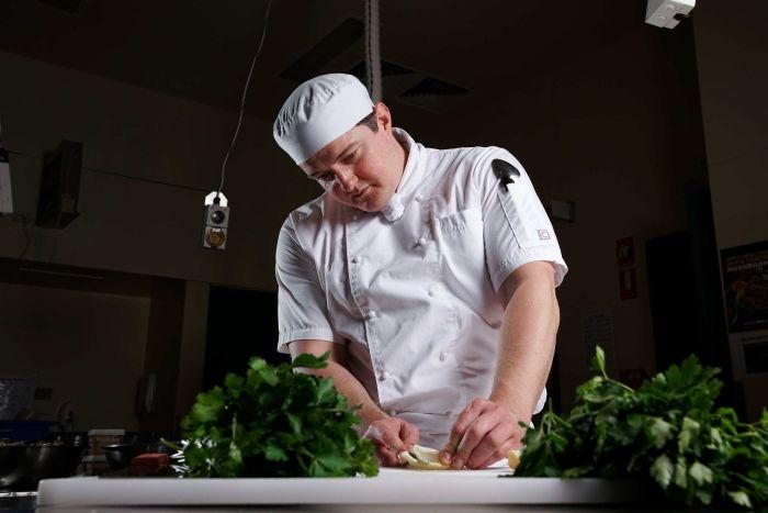 A man wearing a cook's outfit cutting up vegetables