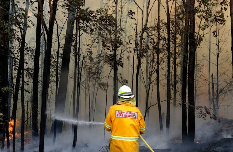 A firefighter extinguishes a blaze in Australia. Climate change is driving rising temperatures and natural disasters. | Rick Rycroft/AP/Shutterstock