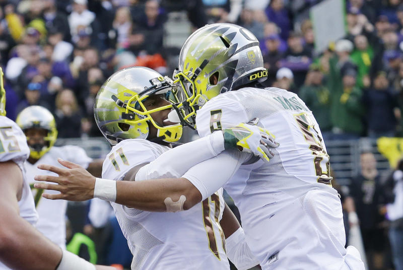 Oregon quarterback Marcus Mariota, right, celebrates with wide receiver Bralon Addison after Mariota scored a touchdown against Washington in the second half of an NCAA college football game, Saturday, Oct. 12, 2013, in Seattle. Oregon won 45-24. (AP Photo/Ted S. Warren)