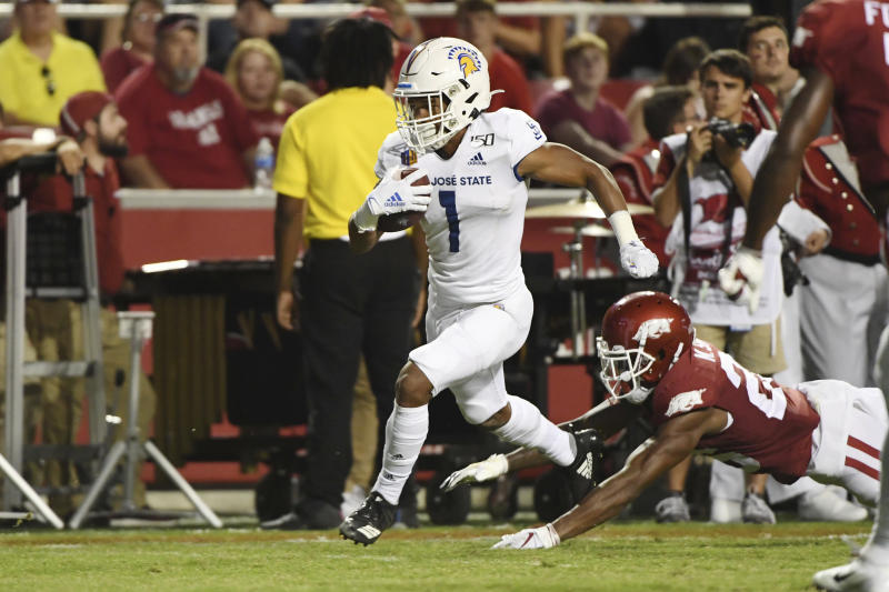 San Jose State receiver Isaiah Holiness slips past Arkansas defender Micahh Smith to score a touchdown during the first half of an NCAA college football game, Saturday, Sept. 21, 2019, in Fayetteville, Ark. (AP Photo/Michael Woods)