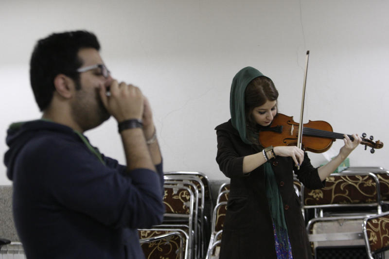 """In this picture taken on Friday, Feb. 1, 2013, female Iranian violinist Nastaran Ghaffari and Danial Izadi with his harmonica practice for their band called """"Accolade"""" in a basement of a house in Tehran, Iran. Headphone-wearing disc jockeys mixing beats. It's an underground music scene that is flourishing in Iran, despite government restrictions. (AP Photo/Vahid Salemi)"""