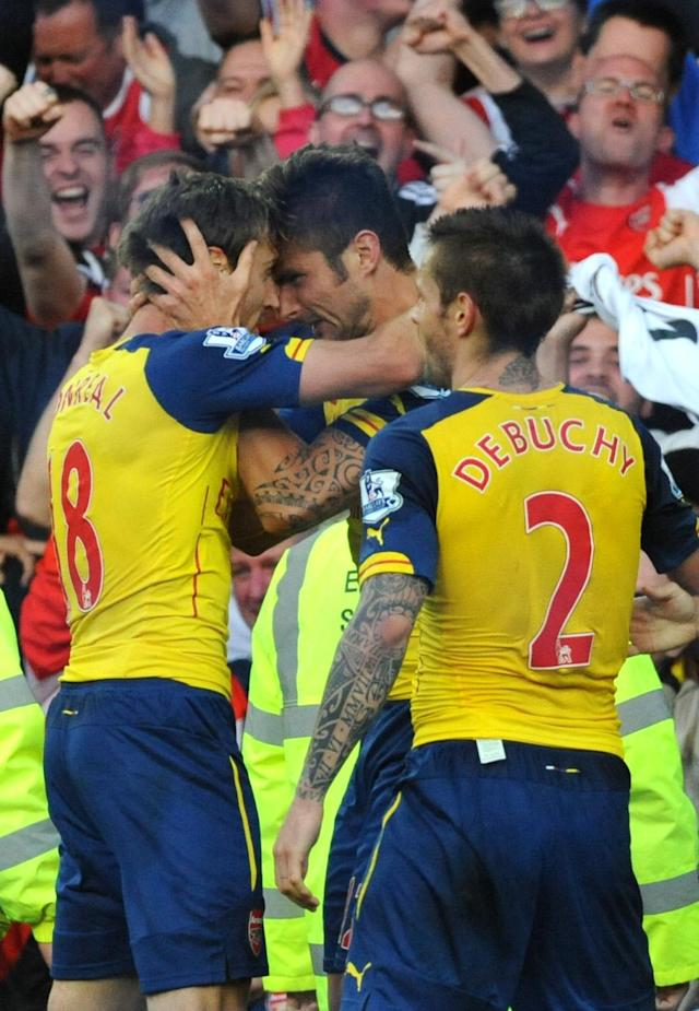 Arsenal's Olivier Giroud, second from left, is congratulated by Nacho Monreal after scoring against Everton during the English Premier League soccer match between Everton and Arsenal at Goodison Park, in Liverpool, England, Saturday, Aug. 23, 2014. (AP Photo/Rui Vieira)