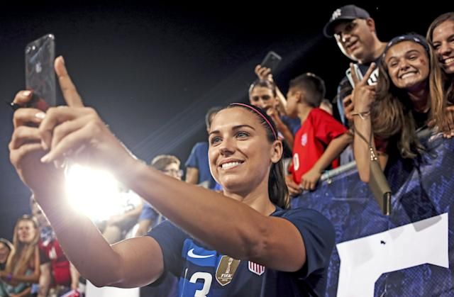 Morgan snapping a selfie with fans. | Getty Images