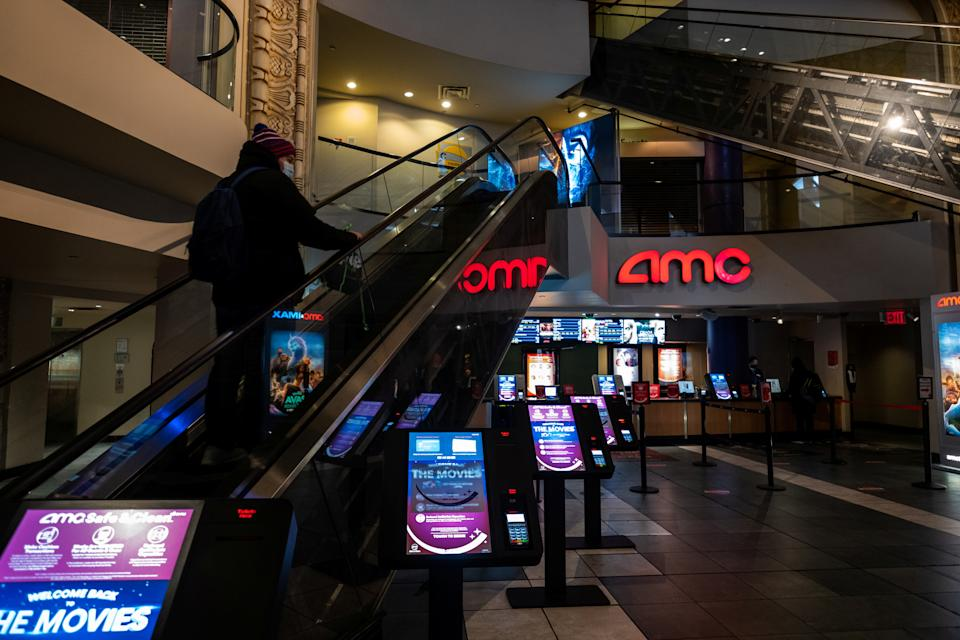 A person wearing a protective mask rides an escalator at the AMC movie theatre in Times Square, amid the coronavirus disease (COVID-19) pandemic, in the Manhattan borough of New York City, New York, U.S., March 6, 2021. REUTERS/Jeenah Moon
